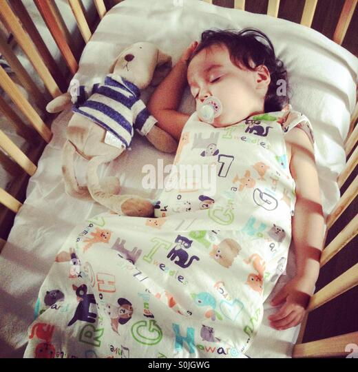 Toddler sleeping in cot with cuddly toy - Stock Image