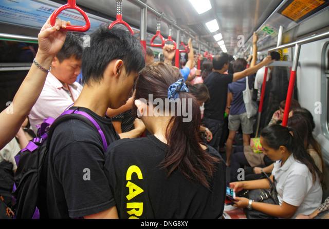 Hong Kong China Island MTR North Point Subway Station public transportation train cabin passengers riders sitting - Stock Image