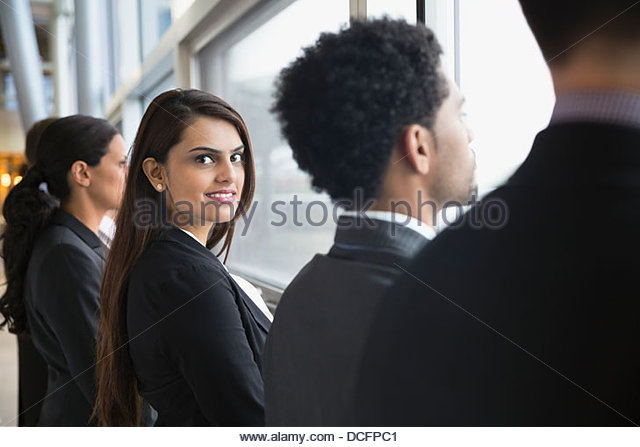Portrait of businesswoman standing with work colleagues - Stock Image