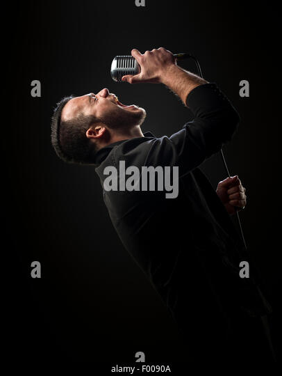 Singer performing with microphone against dark background - Stock Image