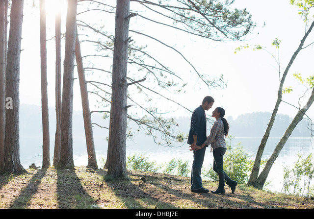 Lakeside.  A couple walking in the shade of pine trees in summer. - Stock-Bilder