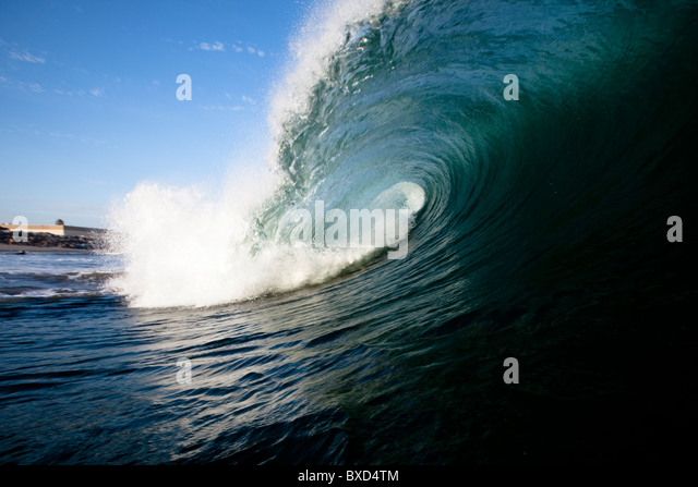 A large wave breaks close to shore. - Stock-Bilder