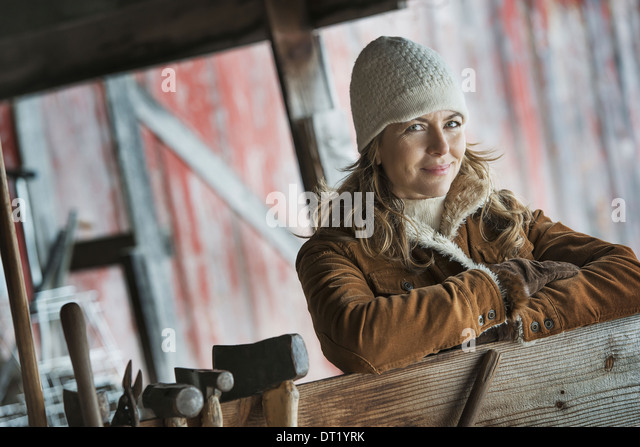A woman in a sheepskin coat A row of hand tools hanging on a post - Stock Image