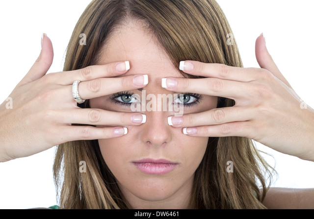 Sad Young Woman Peering Through Fingers - Stock Image