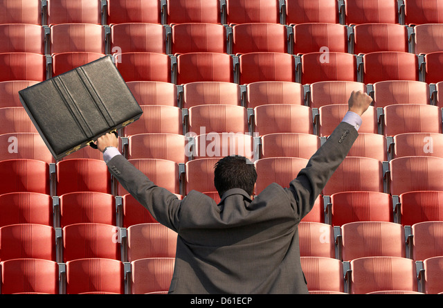Back view of victorious businessman with briefcase facing rows of red seats t stadium - Stock Image