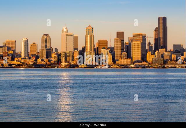 Seattle skyline and Elliott Bay waterfront at sunset, Seattle, Washington, USA - Stock Image