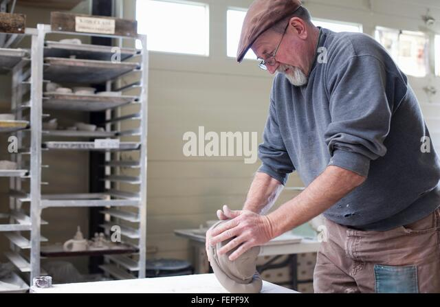 Side view of potter in workshop kneading clay - Stock Image