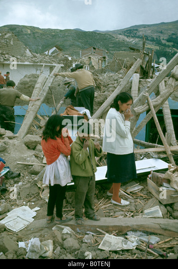 Grieving family among the wreckage of their home in the town of Huaras after the earthquake which struck in the - Stock-Bilder