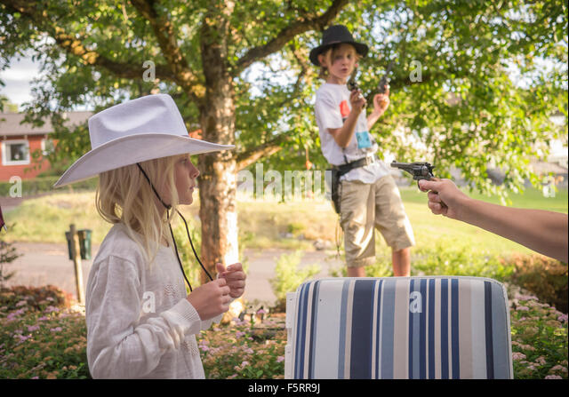 Sweden, Smaland, Anderstorp, Mom playing with her children (8-9, 10-11) in back yard - Stock Image