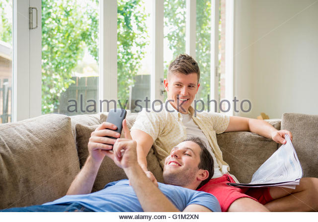 Caucasian gay couple using cell phone and reading newspaper - Stock Image