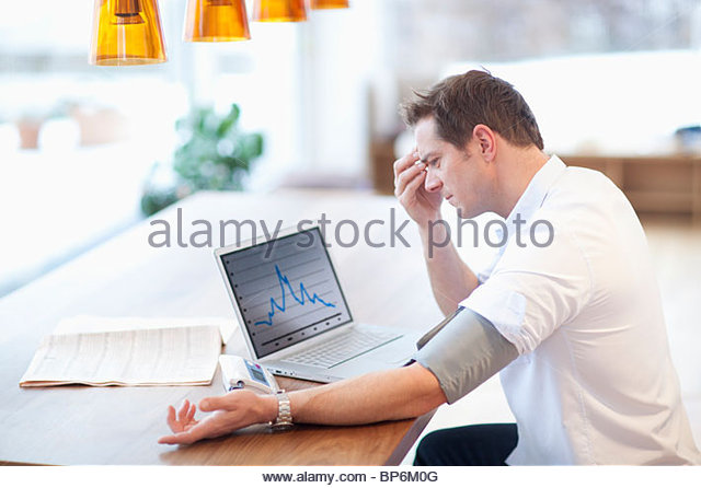 Mid adult man checking his blood pressure at home - Stock Image