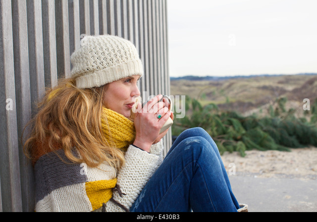 Portrait of mid adult woman leaning against corrugated building at coast - Stock Image