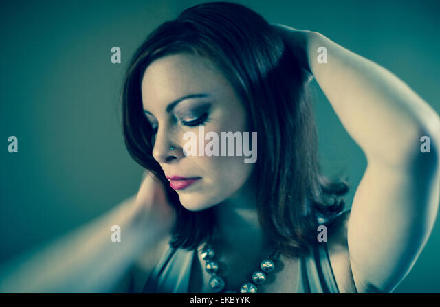 Portrait of mid adult woman, posing, hands behind head - Stock Image