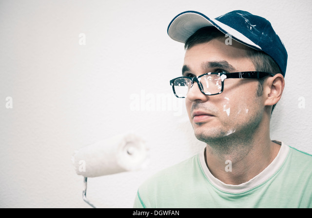 Young man decorating interior with paint roller. - Stock Image