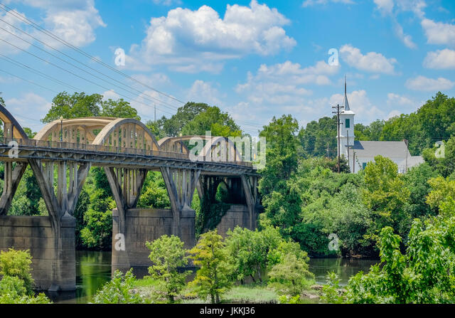 Bibb Graves bridge over the Coosa River in Wetumpka, Alabama with a pretty white church in the background, on a - Stock Image