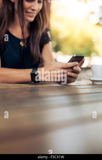 Cropped image of young woman using smart phone in a outdoor cafe. Female reading a text message on her mobile phone. - Stock Image