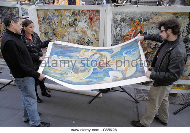 Lower Manhattan New York City NYC NY SoHo West Broadway sidewalk vendor art painting rolling unframed canvas shopping - Stock Image
