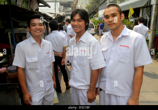Bangkok Thailand Pathum Wan Soi Kasemsan 1 Rama 1 Road Asian man coworkers Honda employees uniform - Stock Image