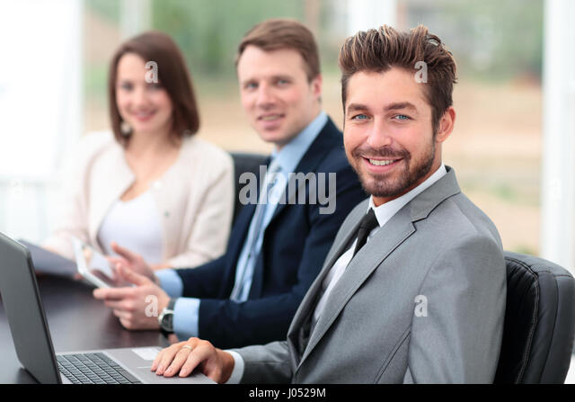 Elegant co-workers looking at camera during meeting in office - Stock Image