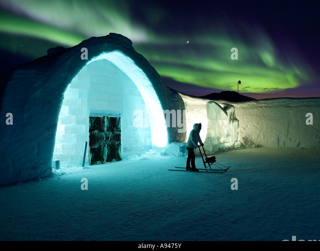 Woman on Kick Sled with Aurora Borealis, Ice Hotel - Stock-Bilder