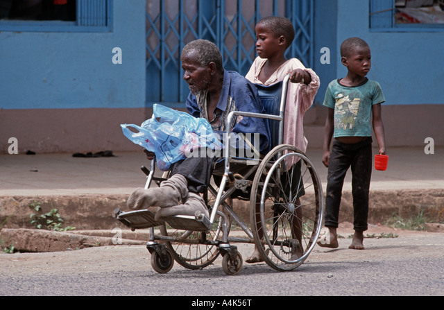 Children pushing a wheelchair with a handicapped relative to beg in the streets of Moshi, Tanzania - Stock-Bilder