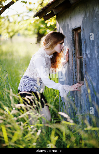 Young woman looks in the window of a hut - Stock Image