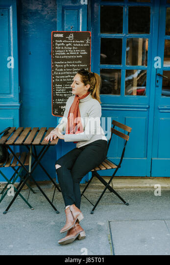 Woman sitting in front of french cafe - Stock Image