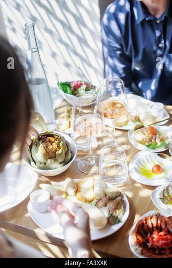 Midsection of couple having meze at Lebanese restaurant - Stock-Bilder