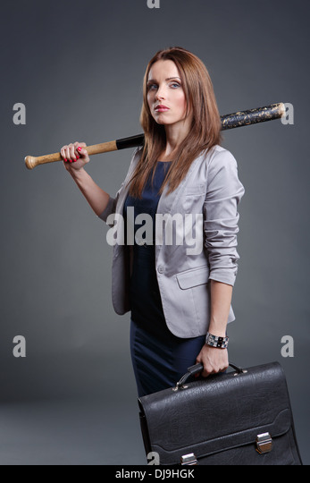 Studio portrait of a courageous and decided woman with baseball bat - Stock Image