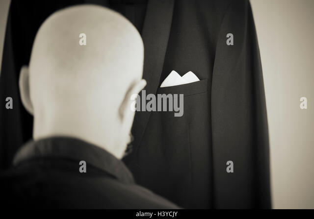 Old man dressing in formal dress. Rear view portrait. Lifestyle moment of retired person. - Stock-Bilder