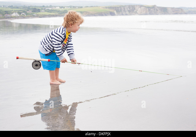 Boy standing on beach with fishing rod - Stock Image