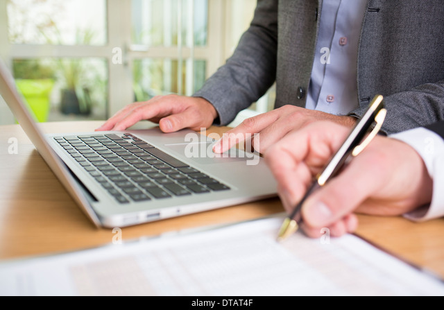 Closeup of Two hands businessmen working together in office with laptop - Stock Image