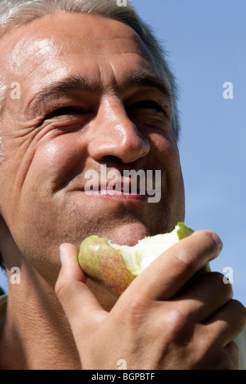 Close-up portrait of happy man eating pear - Stock Image