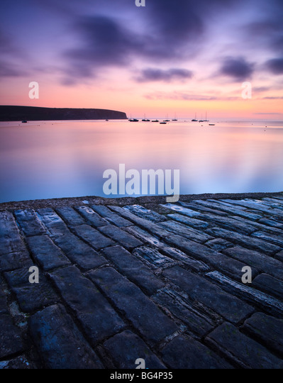 View from the old stone quay, Swanage, Dorset, UK, towards Ballard Down and Old Harry Rocks at dawn - Stock Image