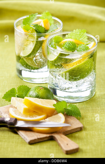 Cold fresh lemonade with lemon and lime on green background - Stock Image