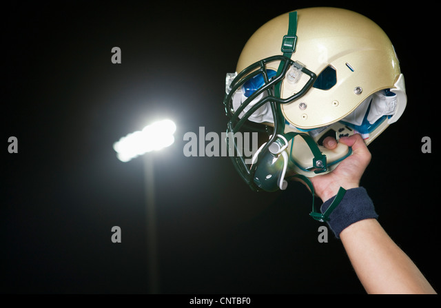 Football player holding up helmet in victory, cropped - Stock Image