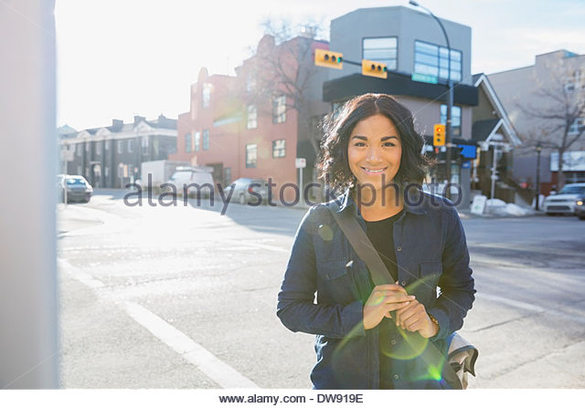 Portrait of smiling woman standing on city street - Stock Image