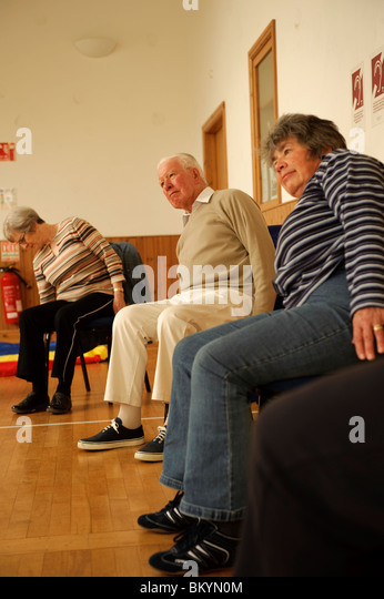senior citizens participating in a low-impact chair aerobics class in a small village hall in west wales UK - Stock Image