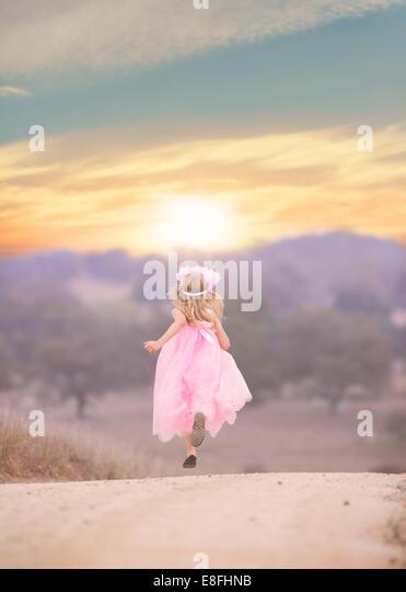 Girl wearing pink dress running down road - Stock Image
