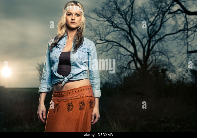 Woman in vintage clothing standing in field with setting sun - Stock-Bilder