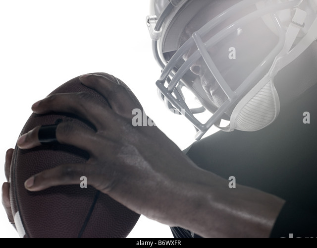 An american football player holding a football - Stock Image