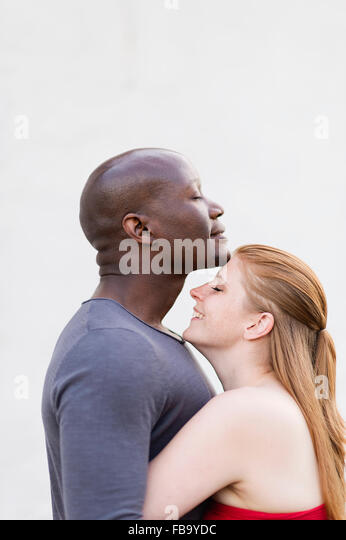 Sweden, Studio shot of mid adult couple embracing - Stock Image