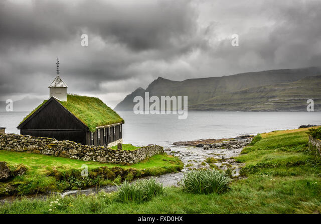 Small village church in Funningur under heavy clouds. Funningur is located on the island of Eysturoy, Faroe Islands, - Stock Image