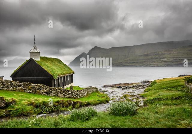 Small village church in Funningur under heavy clouds. Funningur is located on the island of Eysturoy, Faroe Islands, - Stock Image