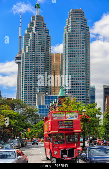 Double decker tour bus with downtown office towers, Toronto, Ontario, Canada. - Stock Image
