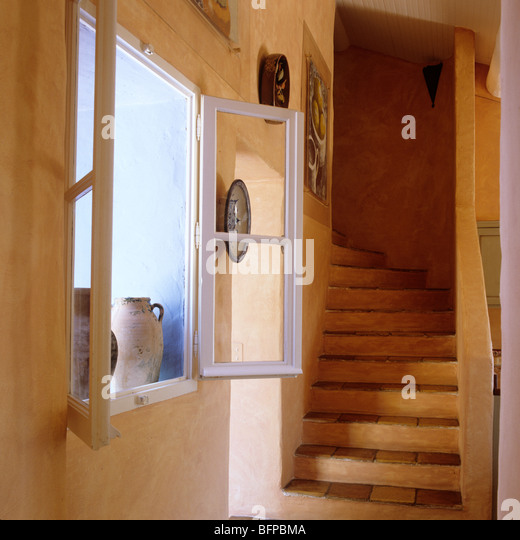 Terracotta staircase and open window in Provençal farmhouse - Stock Image