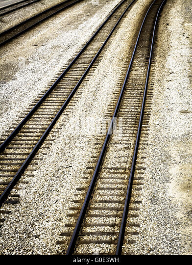 A poetic and empty Overhead view of distantly converging empty train railroad tracks - Stock Image