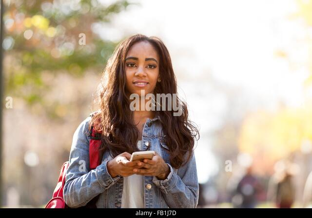 Young woman with long brown hair wearing denim jacket  holding smartphone looking away smiling - Stock Image