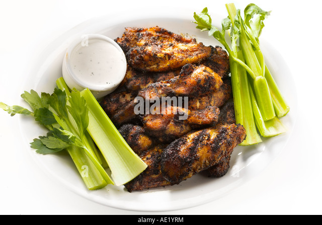 Buffalo Blackened Chicken Wings on a white plate with celery celeries and ranch dressing - Stock Image