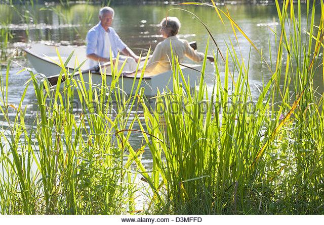 Senior couple in rowboat on sunny lake - Stock Image